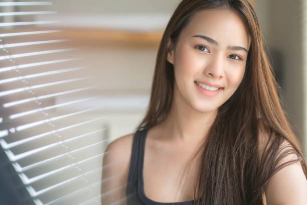 Un retrato de joven mujer asiática sana con sonriendo.cara de primer plano con la piel limpia - foto de stock