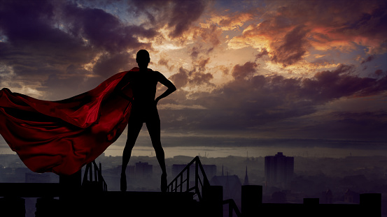istock Portrait of young hero woman with super person red cape guard city 1154130629