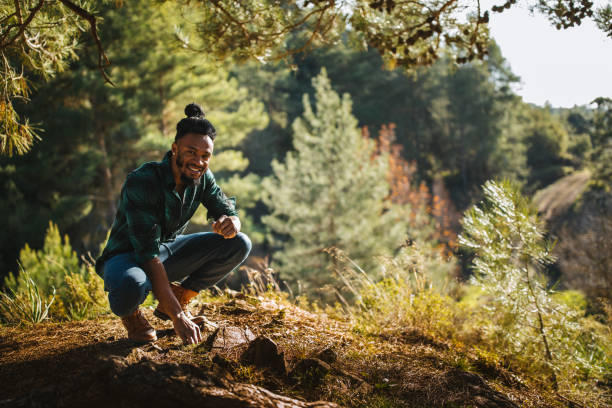 Portrait of young hipster man resting under tree in forest stock photo