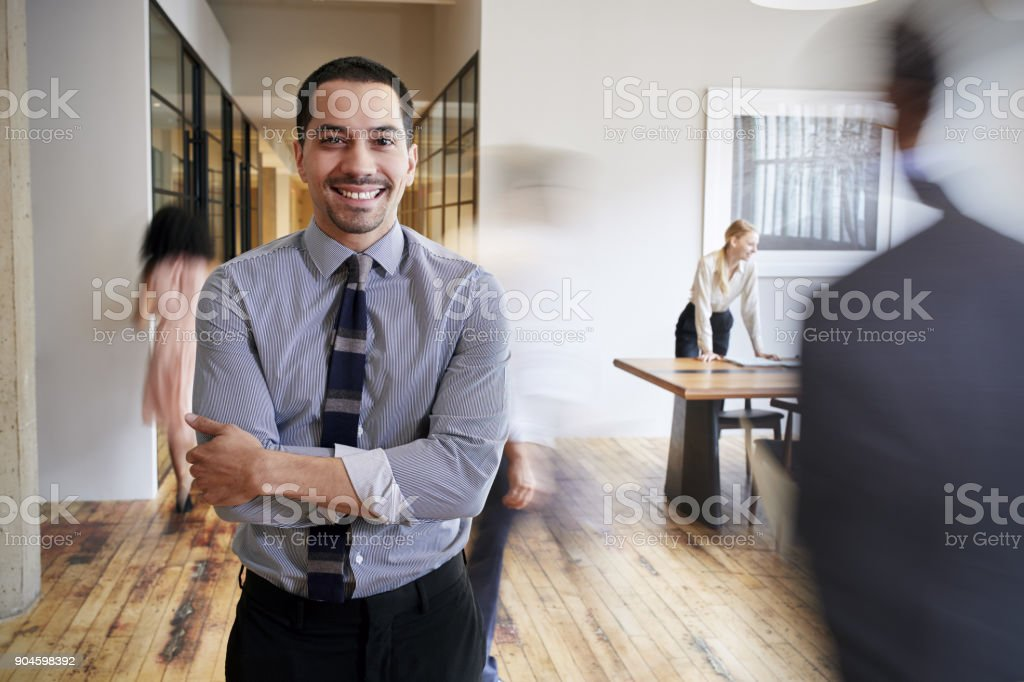 Portrait of young Hispanic man in a busy modern workplace stock photo