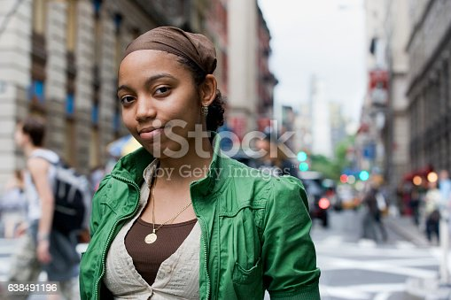 istock Portrait of young Hispanic woman in downtown city 638491196