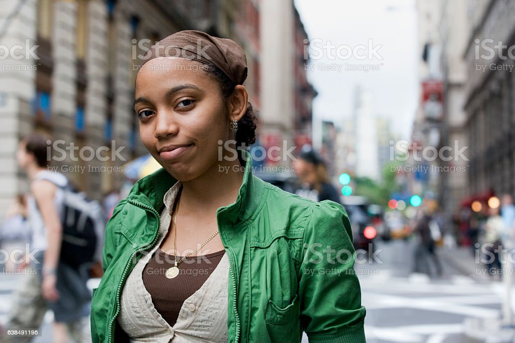 Portrait of young Hispanic woman in downtown city - Photo