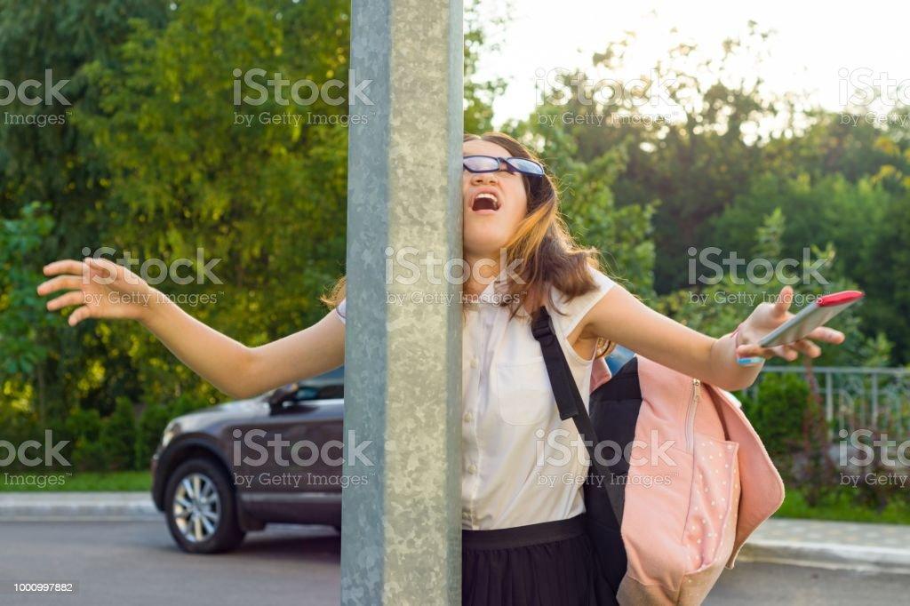 Porträt von Mädchen unaufmerksam, abgelenkt, mit dem Handy. Mädchen stürzte in Straße Post, Telefon gelöscht. – Foto