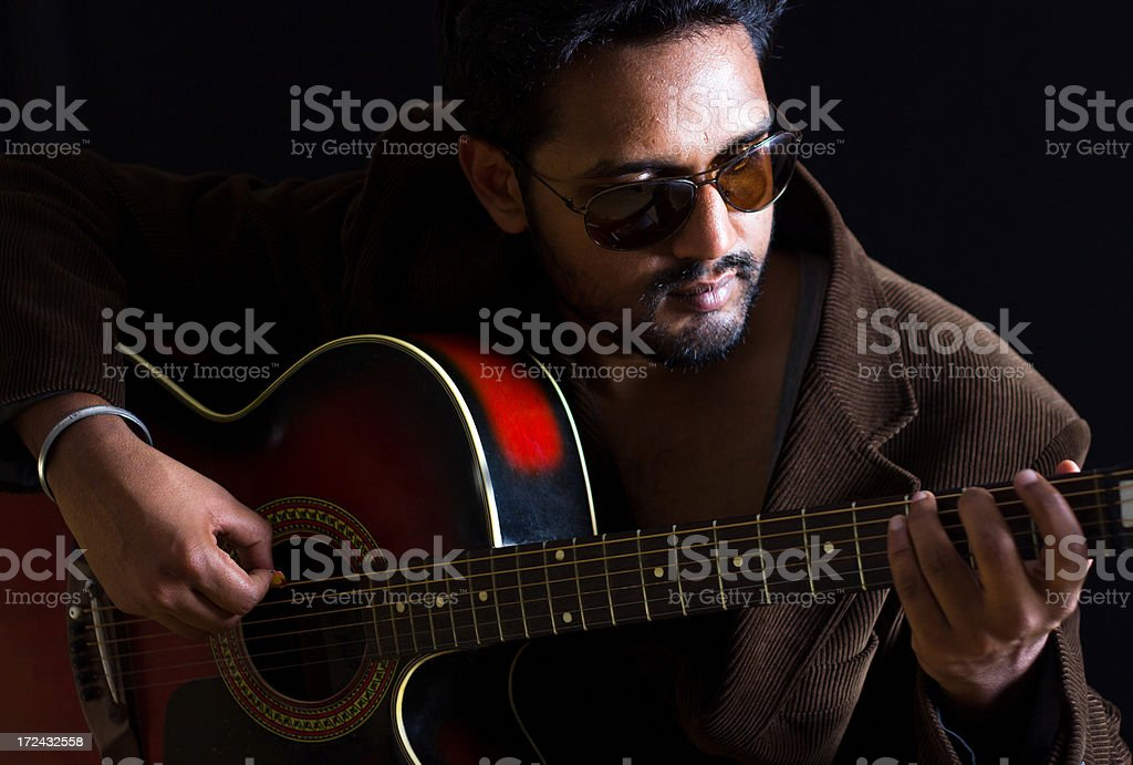 Portrait of young Indian man playing Guitar stock photo