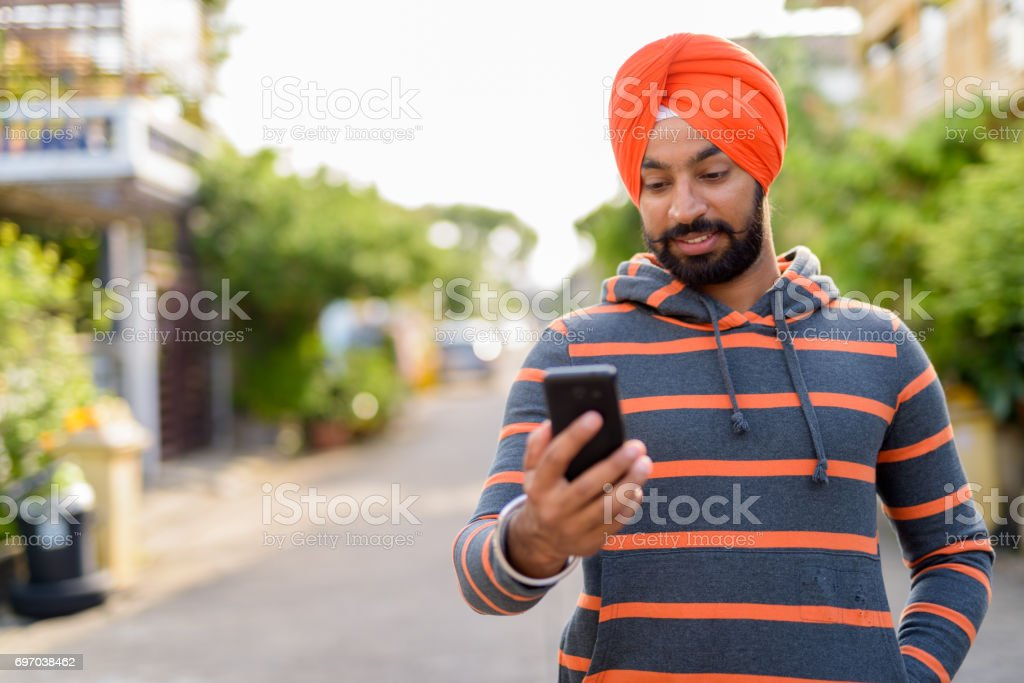 Portrait of young Indian Sikh man wearing hoodie and orange turban in the streets outdoors stock photo