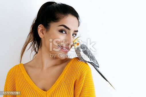 istock Portrait of young Indian woman nuzzling with pet cockatiel 1277752261