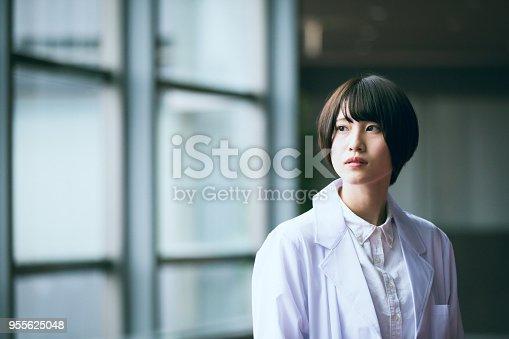 e female researcher standing by window. She wearing white coat.