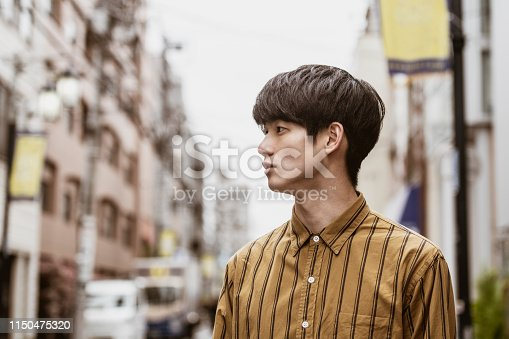 Young man in his 20s with brown hair looking away, street scene, contemplation, individuality