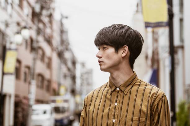 ストライプシャツを着た若い日本人男性のポートレート - 男性のみ ストックフォトと画像