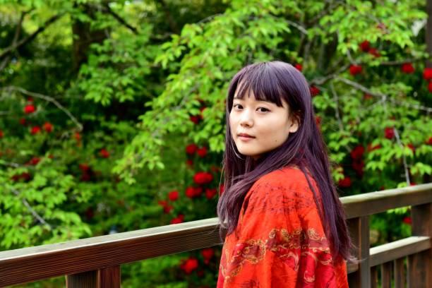 Porträt der jungen japanischen Frau mit Hintergrund von frischem Grün – Foto