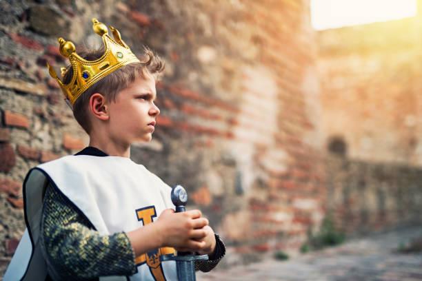 porträt des jungen königs auf den burgmauern - könig stock-fotos und bilder
