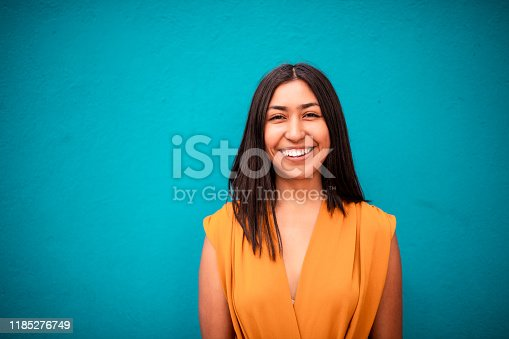 Portrait of young Latin woman with blue background