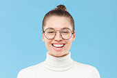 istock Portrait of young laughing girl wearing white sweater, round eyeglasses and hair tied in bun, reacting at joke, isolated on blue background 1227242572