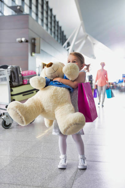 Portrait of young little girl holding her big teddy bear in airport stock photo