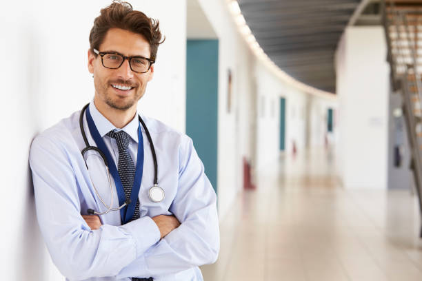portrait of young male doctor with stethoscope, close up - physician stock photos and pictures