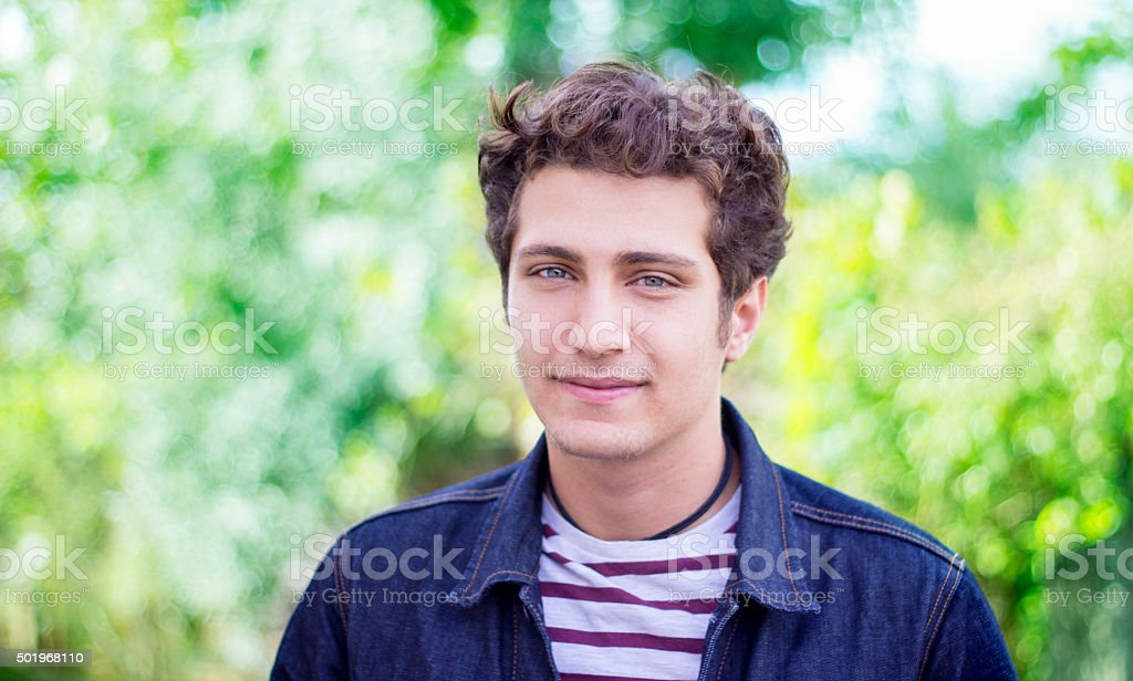 Portrait of young man against blurred trees stock photo