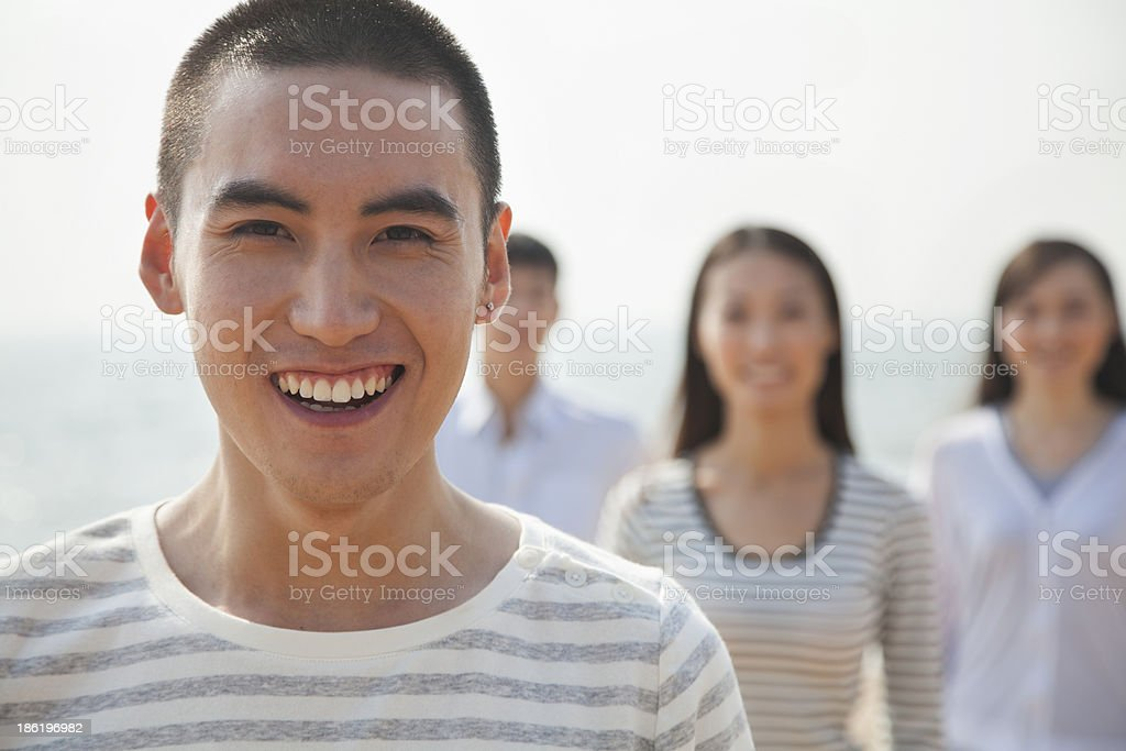 Portrait of Young Man and Friends at Beach royalty-free stock photo