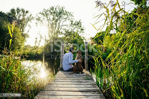 istock Portrait of young man and his dog sitting together on pier 1277107886