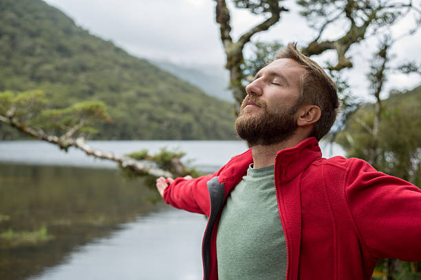 portrait of young man arms outstretched by mountain lake - breathing exercise stock pictures, royalty-free photos & images