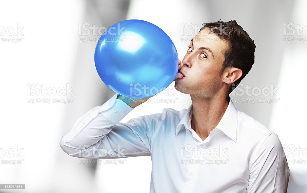 Portrait Of Young Man Blowing aBalloon stock photo