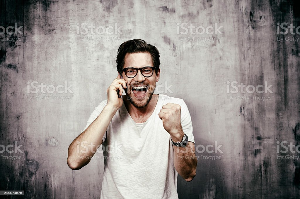 Portrait of young man celebrating on phone stock photo
