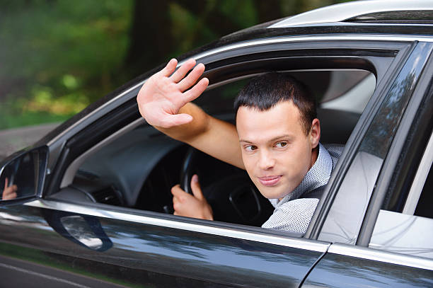 portrait of young man driving car and greeting somebody stock photo
