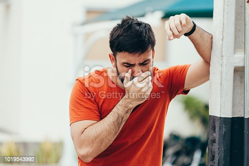 Portrait of young man drunk or sick vomiting outdoors