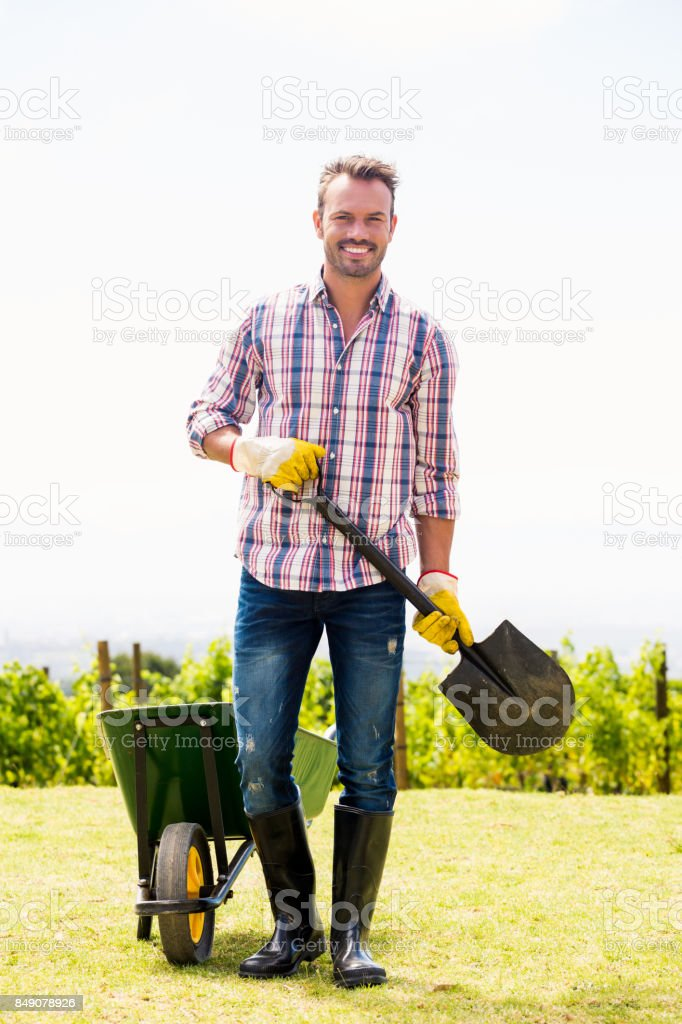 Portrait of young man holding shovel by wheelbarrow stock photo