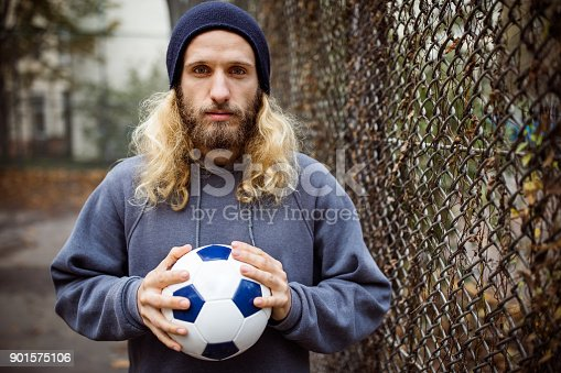 istock Portrait of young man holding soccer ball by fence 901575106