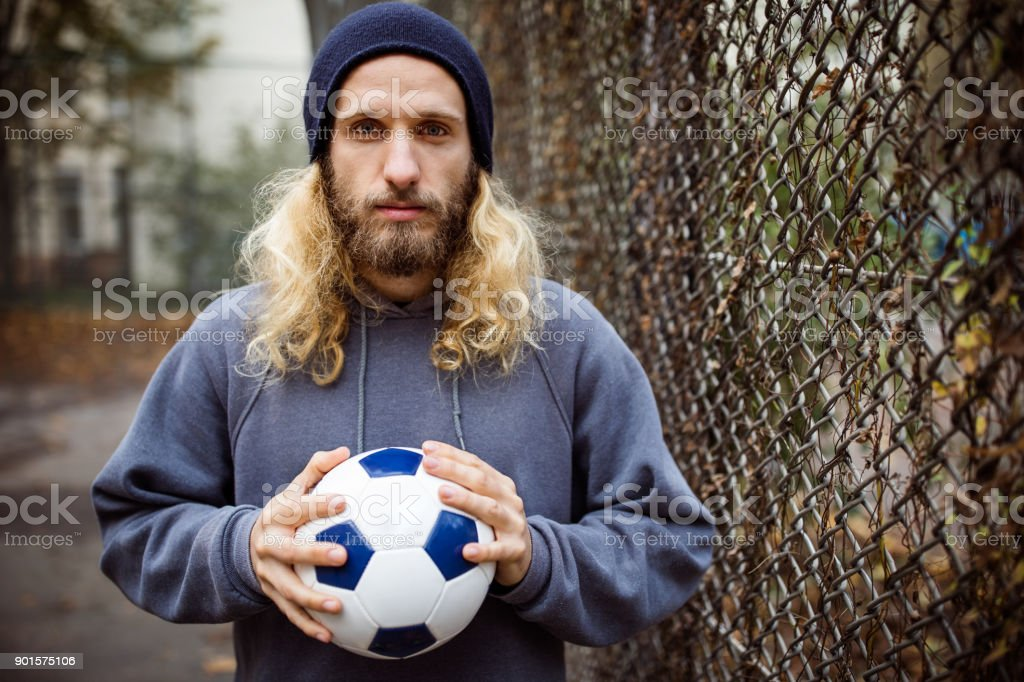 Portrait of young man holding soccer ball by fence stock photo