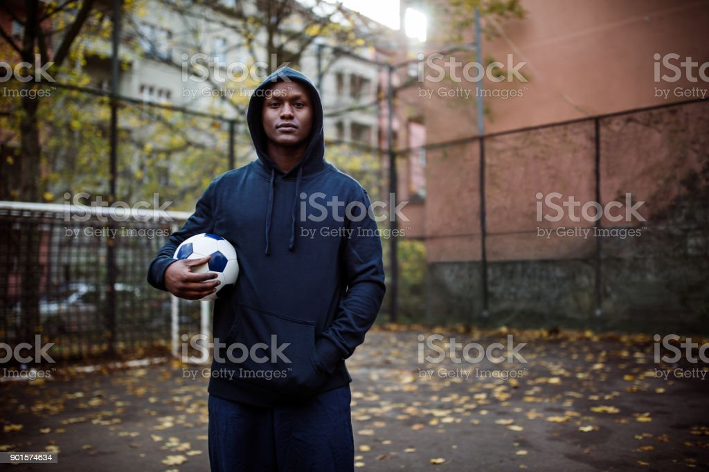Portrait of young man holding soccer ball stock photo