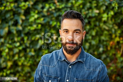 Portrait of confident man in denim shirt. Confident male is in back yard. He is wearing yellow t-shirt.