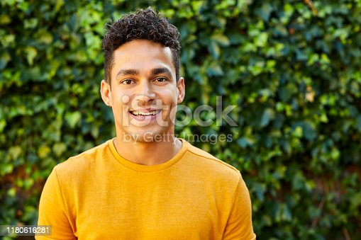 Portrait of smiling young man standing against plants. Confident male is in back yard. He is wearing yellow t-shirt.