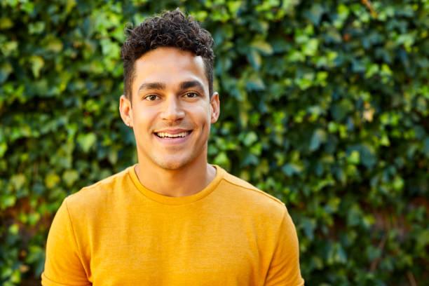 porträt eines jungen mannes in gelbem t-shirt im hinterhof - junger mann stock-fotos und bilder