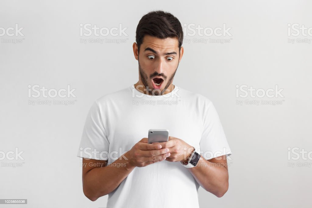 Portrait of young man isolated on gray background, impressed by media content from web on display of her smartphone stock photo