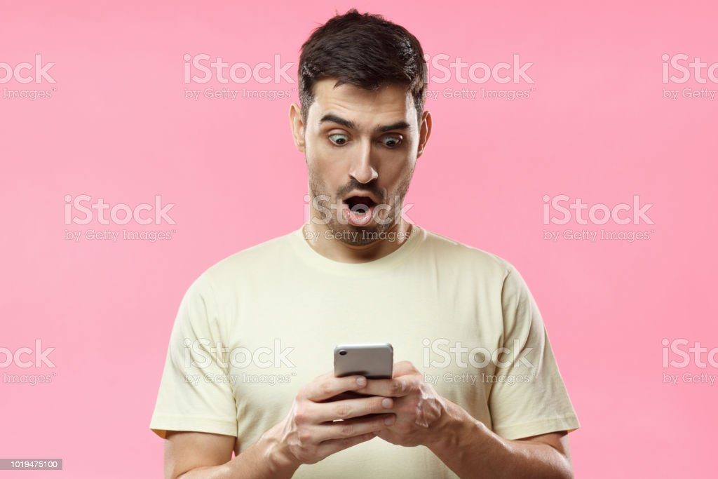 Portrait of young man isolated on pink background, looking agitated at display of her smartphone, impressed by media content from web stock photo