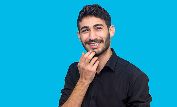 Portrait of young man laughing against blue background stock photo
