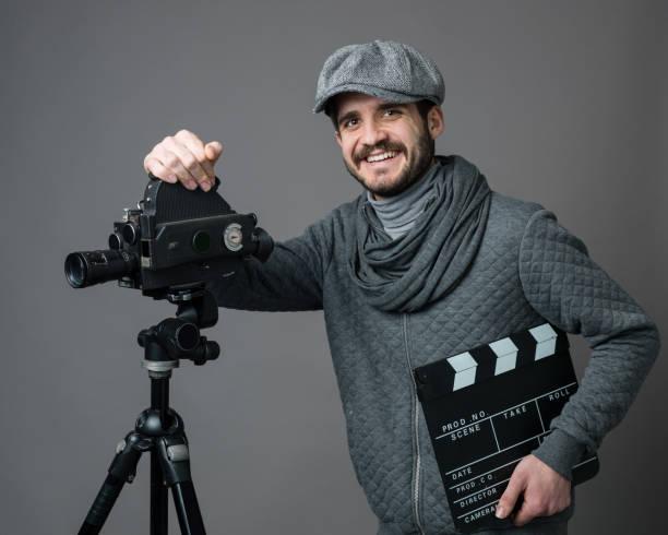 porträt des jungen mannes stützte sich auf kamera - klappe hut stock-fotos und bilder