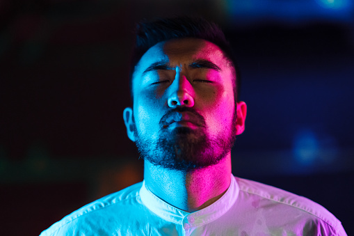 A portrait of a young man lit by a pink and blue neon light in the city.