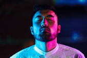 istock Portrait of young man lit by pink and blue neon light in city 1273589951