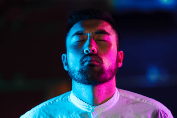 Portrait of young man lit by pink and blue neon light in city stock photo