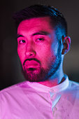 istock Portrait of young man lit by pink and blue neon light in city 1273589997