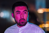 istock Portrait of young man lit by pink and blue neon light in city 1273590558