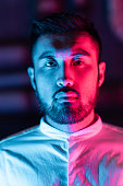 istock Portrait of young man lit by pink and blue neon light in city 1273590793
