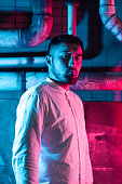 istock Portrait of young man lit by pink and blue neon light in city 1273590844