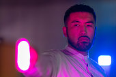 istock Portrait of young man lit by pink and blue neon light in city 1273591181