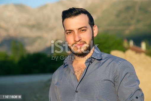 Portrait of  young man looking at camera against tree area
