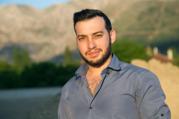 portret van jonge man te kijken naar camera tegen boom gebied - turkse etniciteit stockfoto's en -beelden