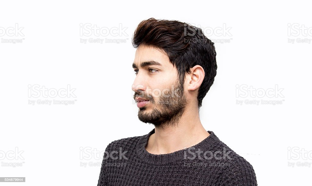 Portrait of young man looking away seriously over white backgrou stock photo