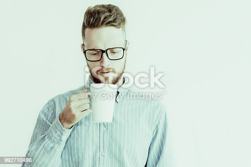 istock Portrait of young man looking in cup with surprise 992710496